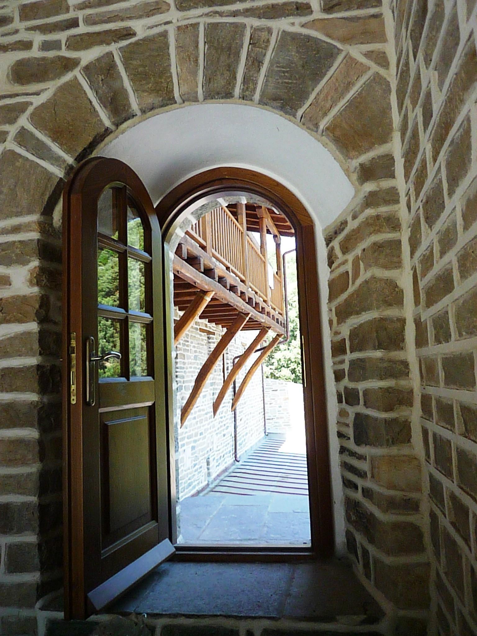 Ανοικτή ξύλινη τοξωτή πόρτα με τζάμια και καϊτια