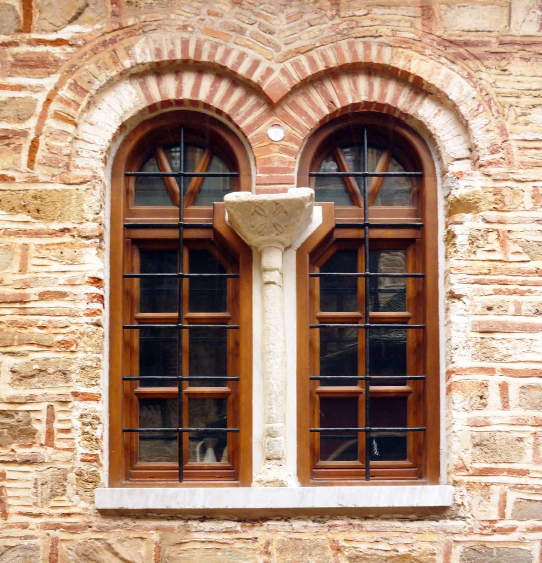 τοξωτά ξύλινα παράθυρα ακανόνιστου σχεδίου με καϊτια και σιδεριές