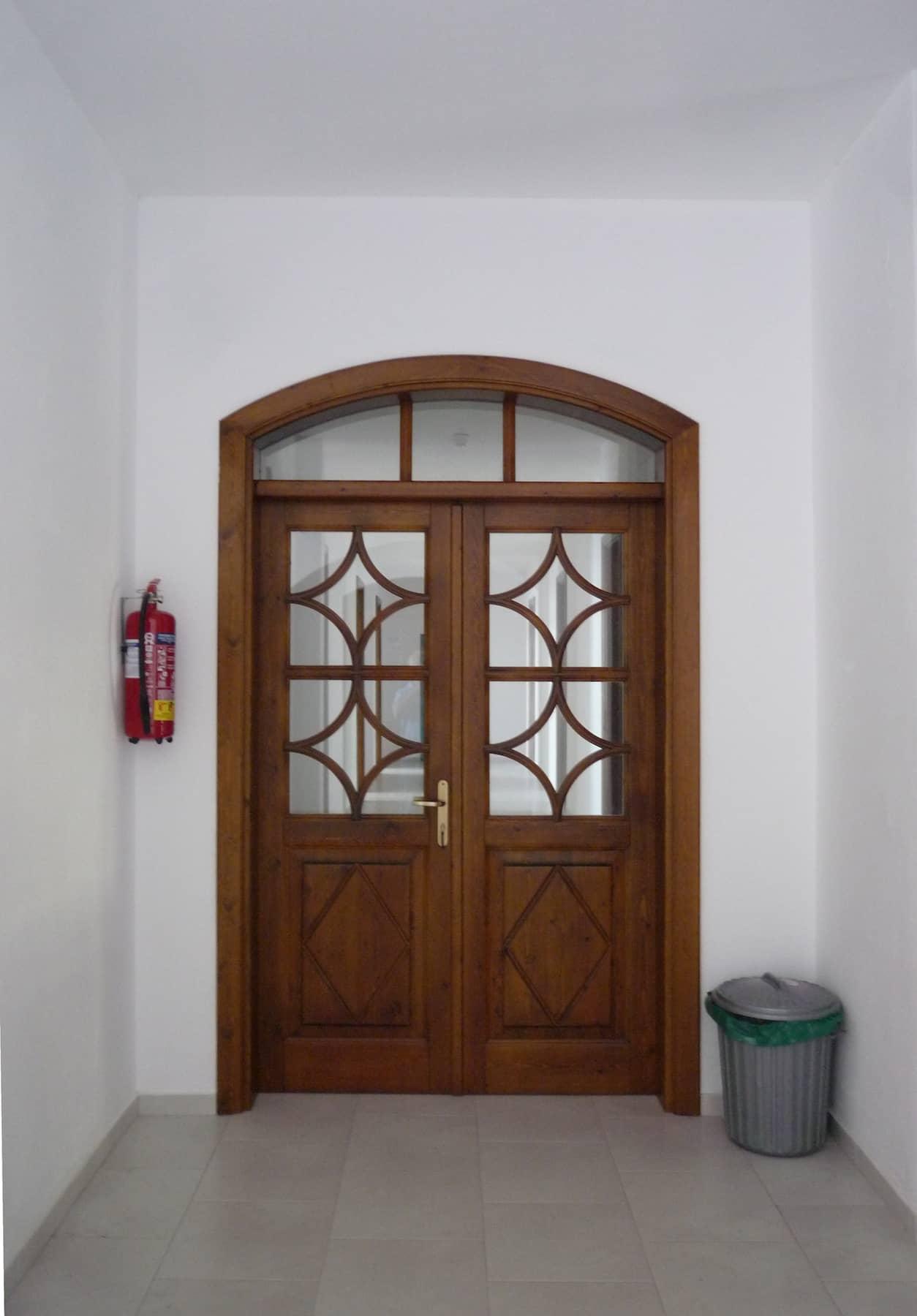 τζαμωτή ξύλινη πόρτα με τοξωτό φεγγίτη