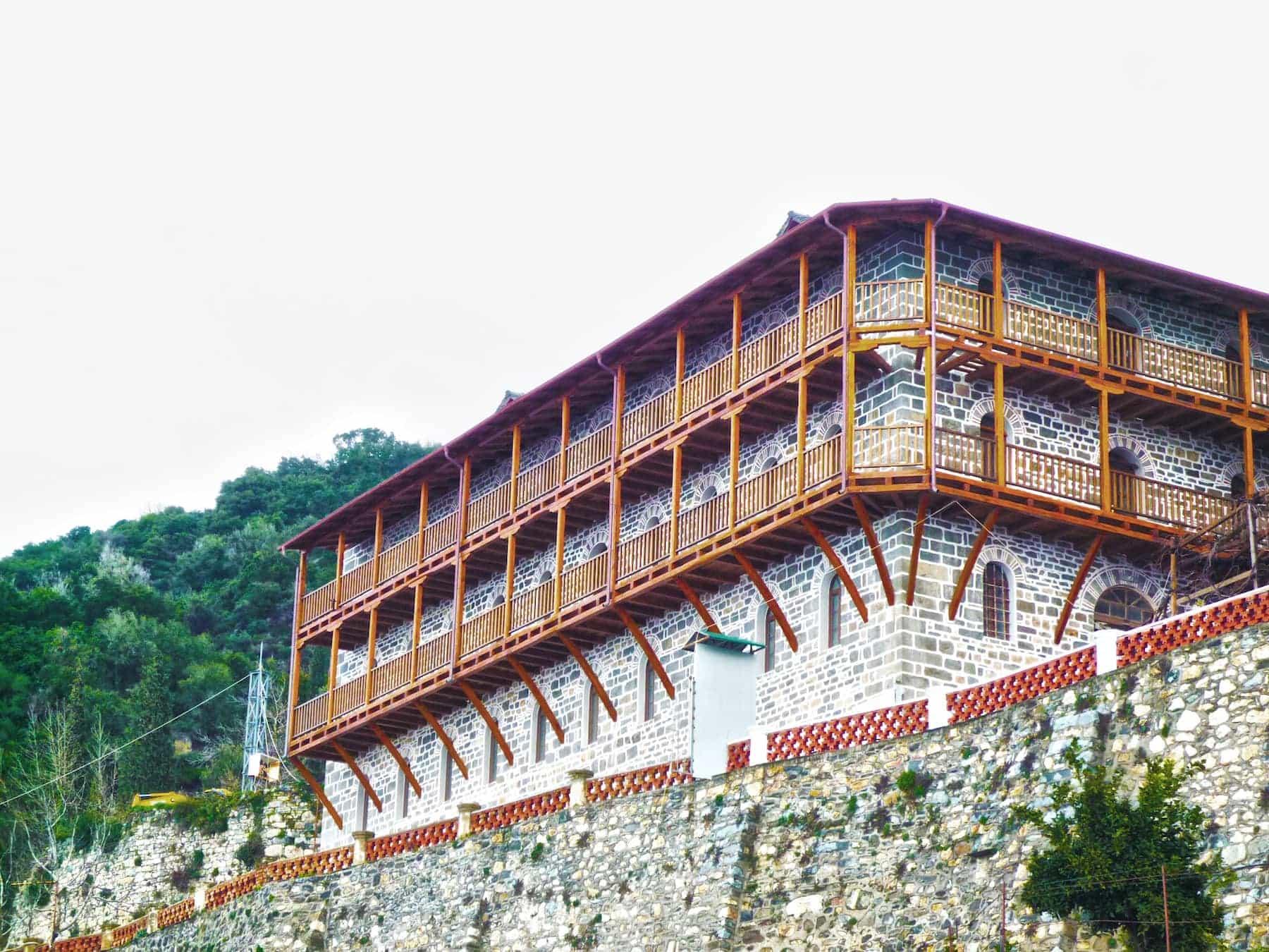 πετρόχτιστο συγκρότημα με ξύλινα κουφώματα ATHOS και περιμετρικό διόροφο ξύλινο μπαλκόνι