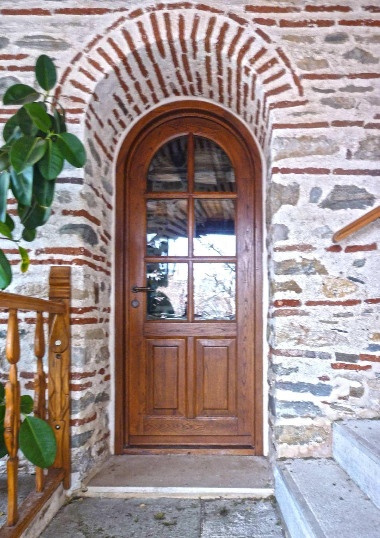 τοξωτή μονόφυλλη πόρτα με τζάμι και ταμπλάδες