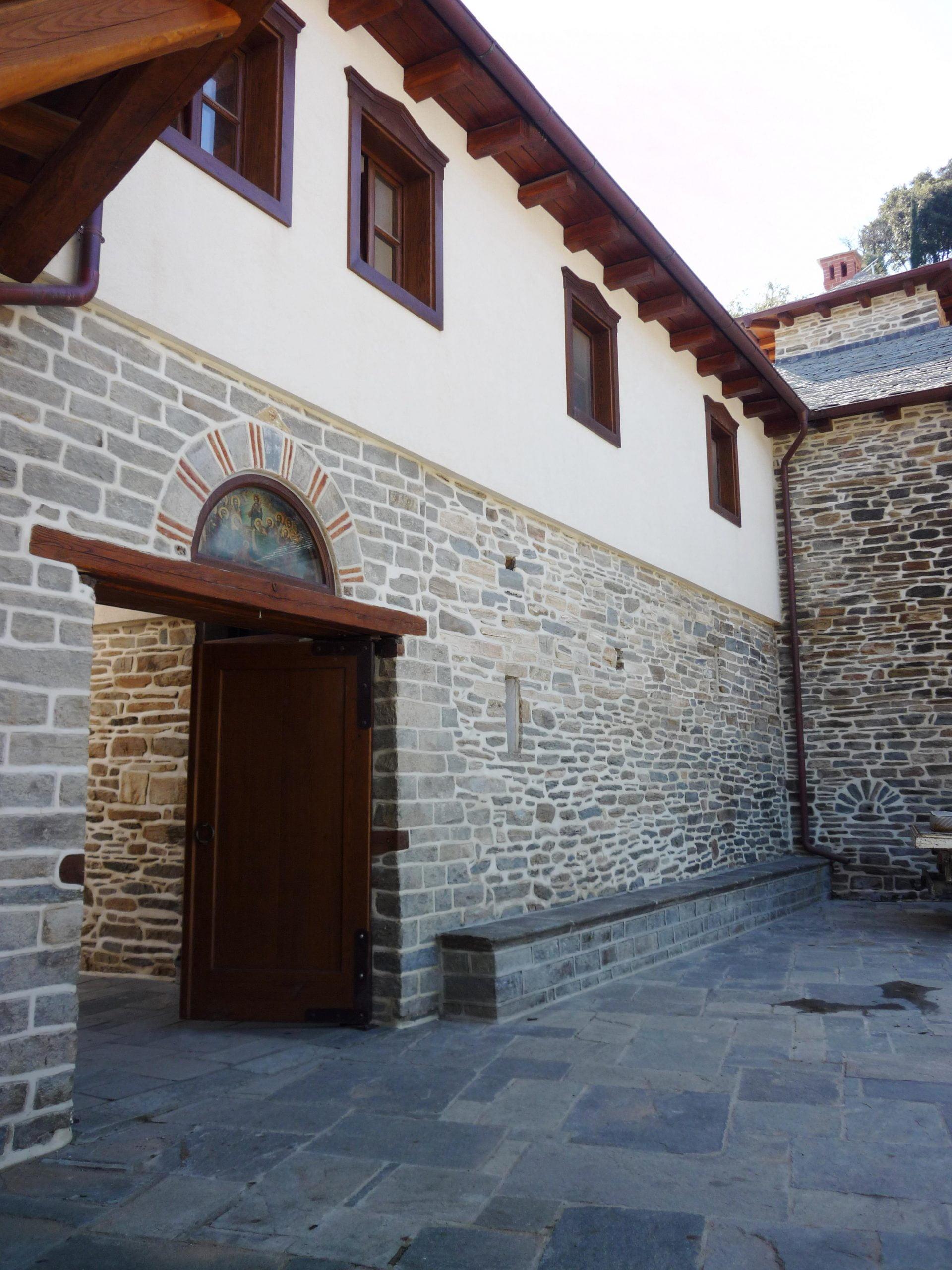 Ξύλινη αυλόπορτα και ξύλινα παράθυρα με αετώματα