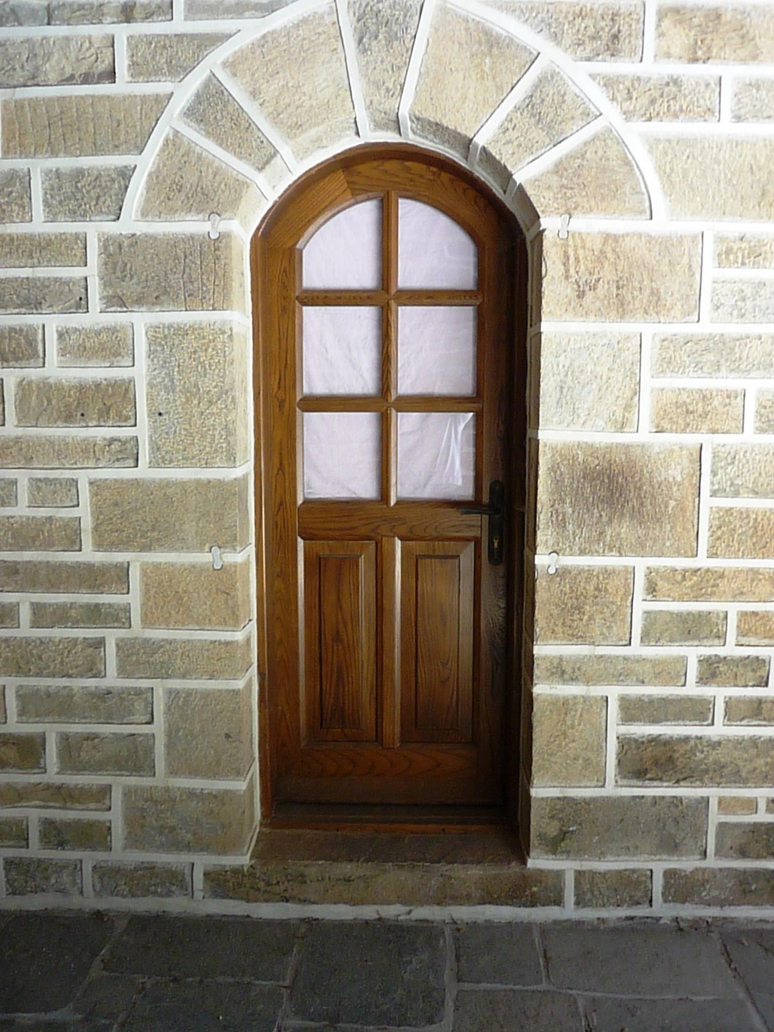 Ξύλινη τοξωτή πόρτα με τζάμια και καϊτια