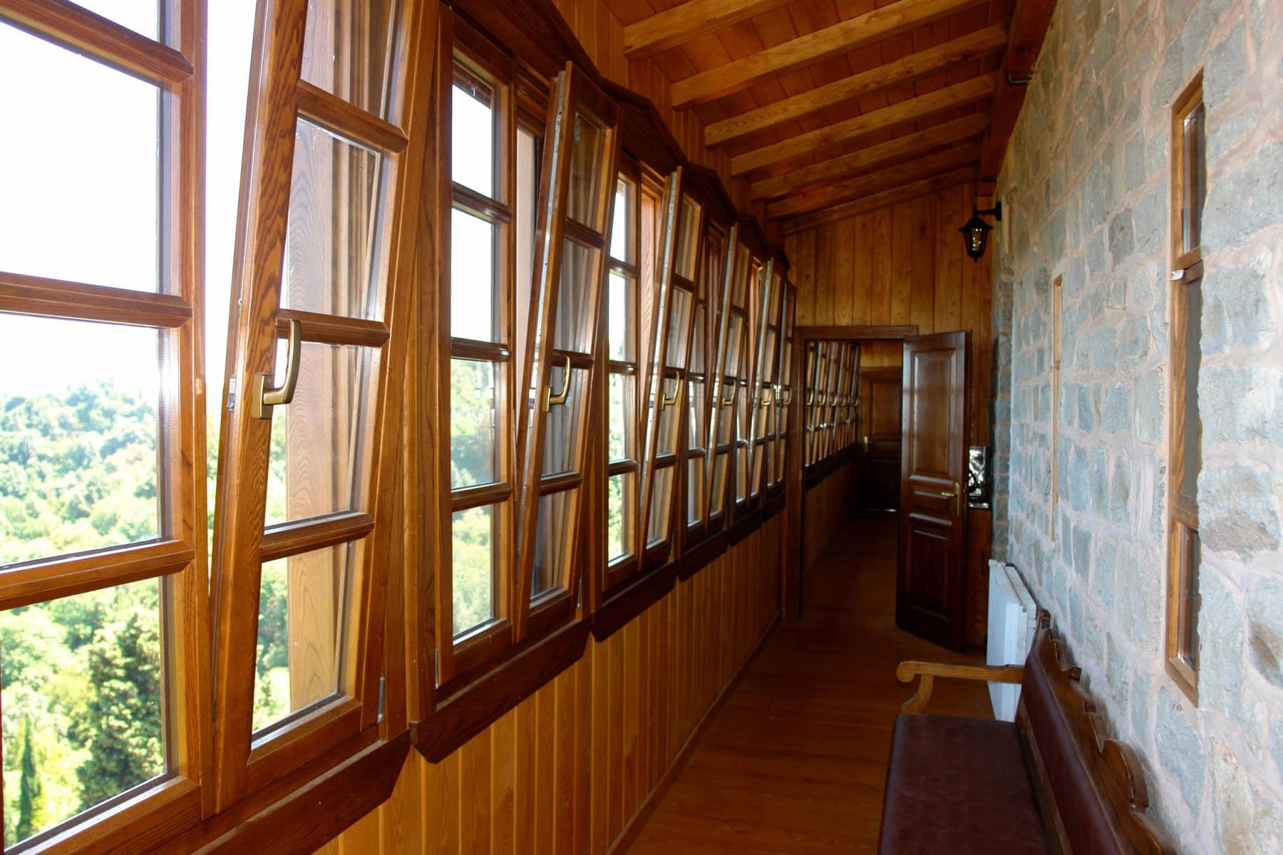 από ανακλινόμενα δίφυλλα ξύλινα παράθυρα με αέτωμα και ειδικό κατωκάσι